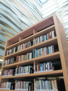 Walls of concrete and glass reach to the sky around the bookcases.