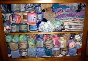 My yarn cabinet is stuffed with yarn, books and finished doilies.