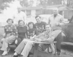 Normie and his wife, Wini, in matching sweaters in the center. My grandfather stands behind my grandma.  Wini's parents are the women sitting on the left and the man standing on the right.  At the bungalows in the Catskills in the 1950s.