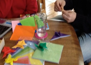 Making origami frogs before the seder.
